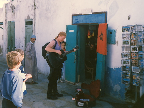 Tom with an audience looking incongruent with orange hair and guitar in a medina in Morocco. Man wearing a djellaba looking on with curiousity